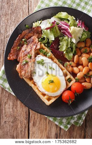 Breakfast With Fried Egg, Waffles, Bacon, Mix Lettuce And Beans Close-up. Vertical Top View