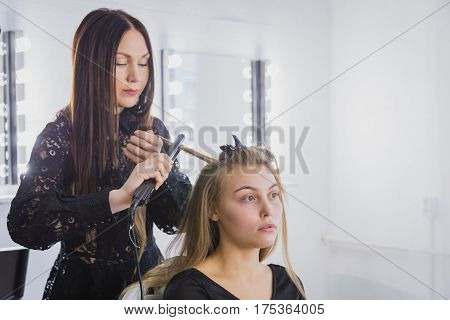 Beautiful young woman is getting her hair straightened at beauty saloon. The hairdresser is standing and holding a fluting iron