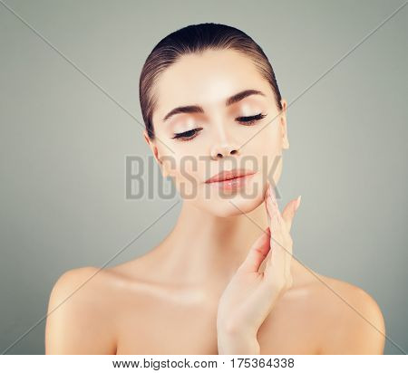 Beautiful Spa Model Woman with Healthy Skin Touching her Hand her Face. Spa Beauty Skin Care and Cosmetology Concept