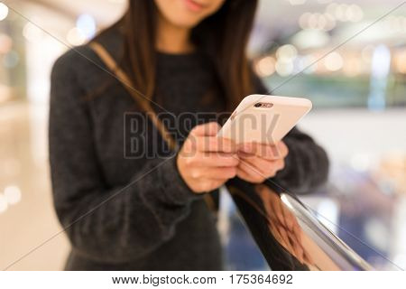 Woman working on cellphone in shopping mall