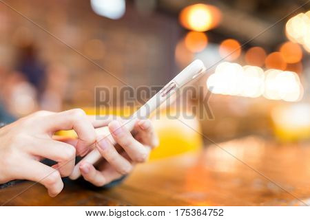 Woman sending sms on mobile phone in coffee shop