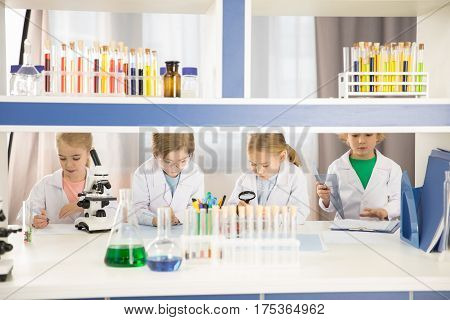 Schoolchildren in lab coats studying together in chemical laboratory