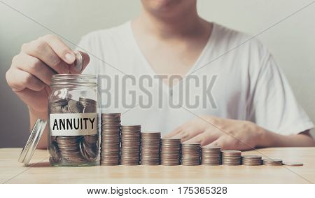 Hand putting coins in jar word annuity with money stack step growing growth saving money Concept finance business investment