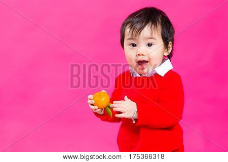 Excited little baby boy holding a Mandarin orange