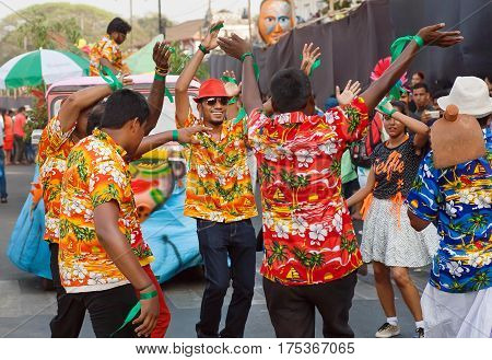 PANAJI, INDIA - FEB 25, 2016: Happy people in hawaiian shirt dancing on the bright parade of the traditional Goa carnival on February 25, 2017. Carnaval is celebrated in Goa since 18th century