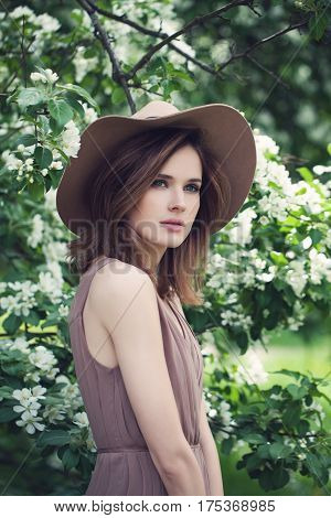 Magnificent Model Woman Outdoors. Portrait of Beautiful Young Woman with Brown Bob Hairstyle and Summer Hat