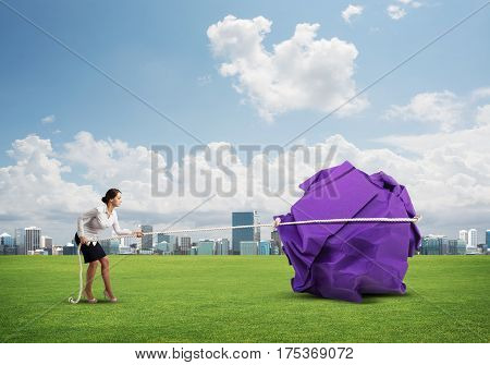 Young woman outdoors making huge paper ball move
