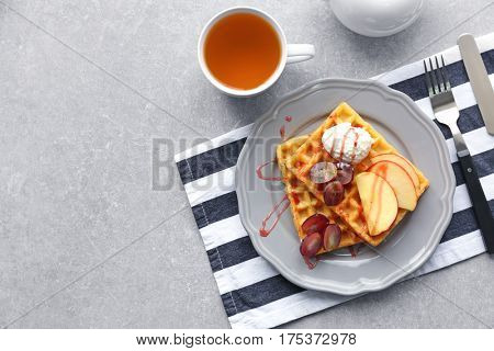 Tasty waffles with delicious fruits, ice-cream and syrup on grey plate