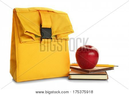 Modern lunch bag, stationery and appetizing red apple on white background