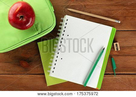 Exercise book and lunch bag with red apple on wooden background