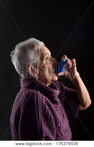Senior woman with an inhaler on a white background