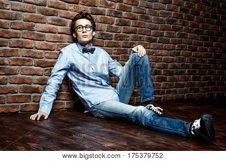 Serene melancholic young man sitting on the floor and looking pensively forward. Brick wall background. Copy space.
