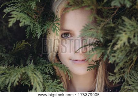 Cute young adult female hiding in forest, close up woman portrait