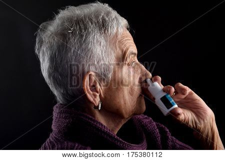 Old woman with nasal spray on a black background
