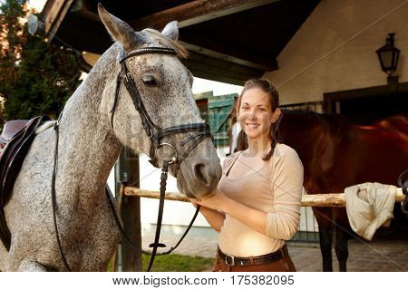 Happy young woman smiling, standing by her horse over stall.