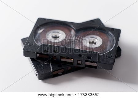Two black audio cassette on white background.