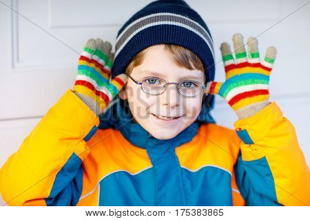 Portrait of little cute school kid boy with glasses and colorful winter fashion clothes. Child smiling and having fun with the camera. Winter, spring or autumn fashion. Boy with missing front teeth