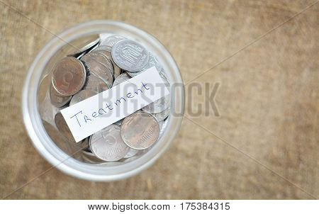 Glass Jar Filled With Coins Labeled With Words Treatment. View From Above. Background Of Burlap. The