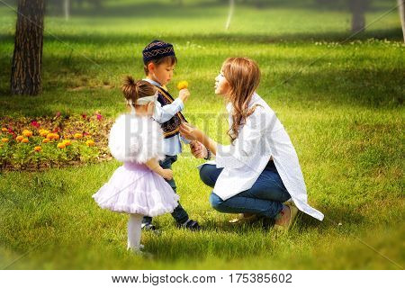 Kazakh mother with children. Son and daughter in the summer park