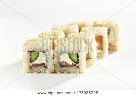 Japanese Sushi Food - Sushi Roll with Salmon, Cucumber and Cream Cheese inside. Sesame outside. Maki Sushi on White Background