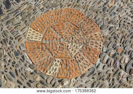Patterned floor with sea pebbles and red bricks in the park Montjuic Barcelona Catalonia Spain