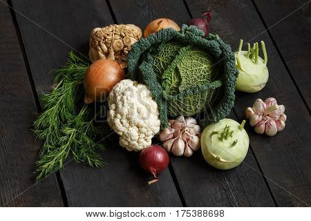 Spring vegetables on a dark background: Savoy cabbage, cauliflower, onion, garlic, kohlrabi, celery root dill. Top view. Lay flat