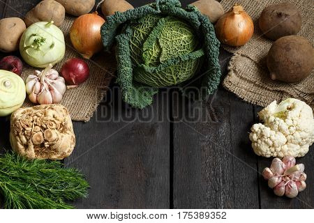 Spring vegetables on a dark background: Savoy cabbage, cauliflower, onion, garlic, kohlrabi, celery root, dill. Top view Lay flat