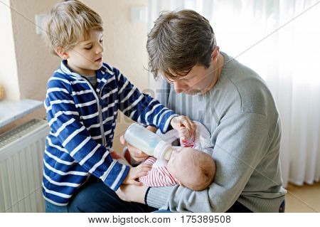 Father and kid boy feeding newborn baby daughter with milk in nursing bottle. Formula drink for babies. New born child, little girl laying in bed. Family, hildhood, beginning, bottle-feeding concept.