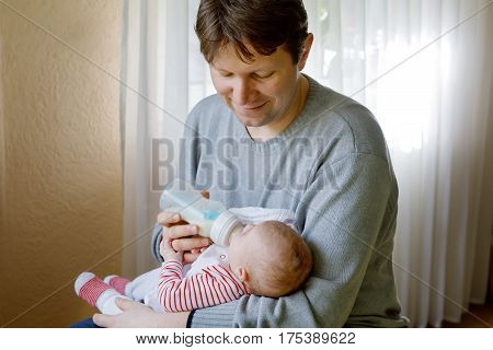 Father feeding newborn baby daughter with milk in nursing bottle. Formula drink for babies. New born child, little girl laying in bed. Family, new life, childhood, beginning, bottle-feeding concept.
