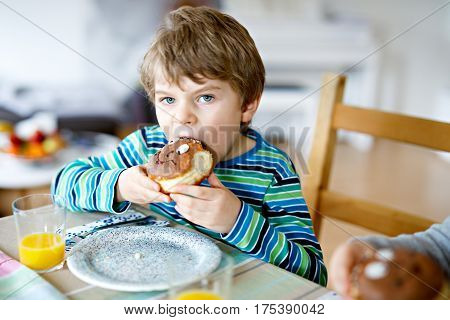 Adorable little school boy eating sweet donut indoor. Blond child in domestic kitchen or in school canteen Cute kid and unhealthy sugared food