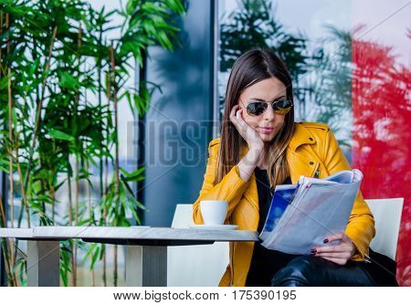 urban girl with sunglasses sit in cafe outdoor reading  magazine  spring day city life concept