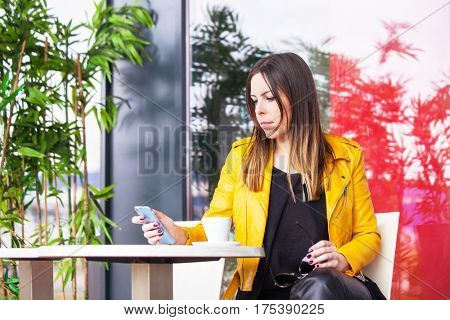 urban girl sit in cafe outdoor with coffee checking messages on smartphone spring day city life concept