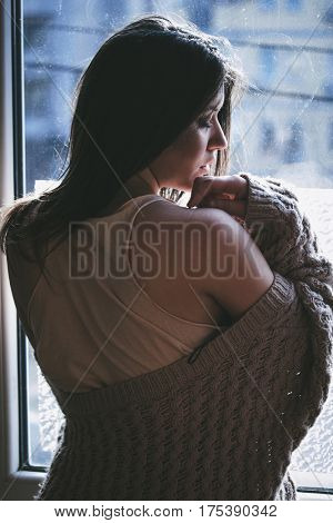 beautiful pensive young woman by the window portrait