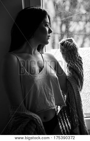 beautiful pensive young woman by the window portrait in bw