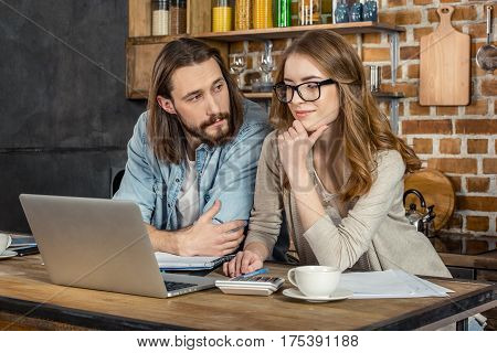 Attractive young couple of freelancers working with laptop at home office