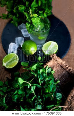 Fresh mojito drink with lime and mint in a glass on black stone board and wooden rustic table