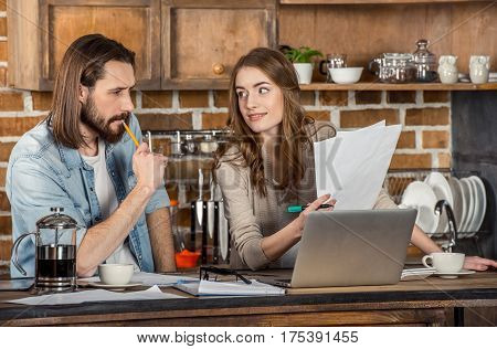 Beautiful young couple working with documents and laptop at home