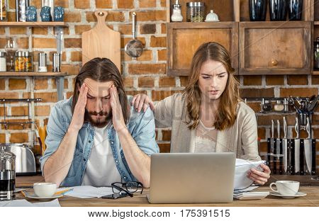 Upset young couple of freelancers working with papers and laptop in kitchen