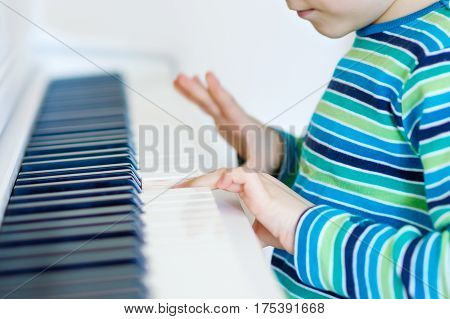 Beautiful little kid boy with headphones playing piano in living room or music school. Preschool child having fun with learning to play music instrument. Education, skills concept.