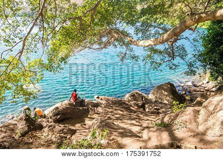 People Enjoying Clear Water Of Chala Lake On The Border Of Kenya And Tanzania, Africa