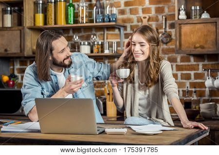 Young smiling couple drinking coffee and talking while using laptop at home