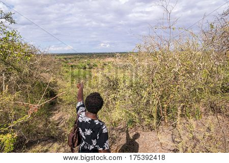 African woman pointing ahead to undeveloped countryside Kenya
