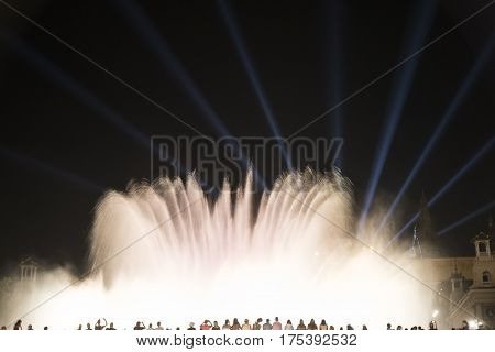 BARCELONA, SPAIN - JULY 30, 2016: Barcelona (Catalunya Spain): the Magic Fountain (Fuente Magica Font Magica) of Montjuic with plays of colorful lights at evening and people in silhouette watching at the show