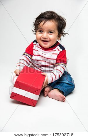 indian baby boy or infant holding red gift box, isolated over white background