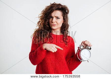 Portrait of a young woman pointing finger on alarm clock isolated on a white background