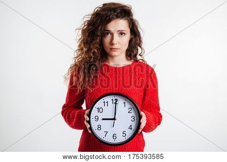 Portrait of a sad young curly woman holding wall clock over white background