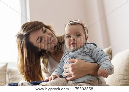Young mother holding her baby girl in her lap playing and enjoying motherhood