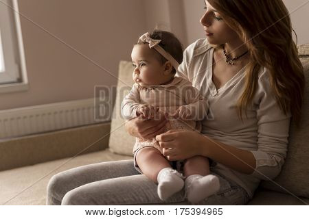 Mother sitting on a living room couch with her baby girl in her lap looking away from the camera pensive