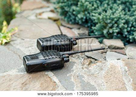 Walkie Talkies on the stones background outside. Concept of Wireless Communications.