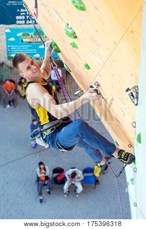 Male Athlete hanging on climbing Wall of national Competitions with very emotional Face. Dnipro, Ukraine, May 20, 2016